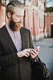 Jeune homme barbu avec le mobile, extérieur Image stock