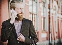 Jeune homme barbu avec le mobile, extérieur Photographie stock