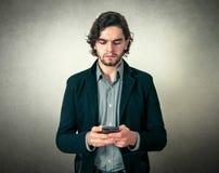 Jeune homme barbu avec le téléphone photos libres de droits