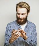 Jeune homme barbu avec le téléphone portable Images stock