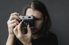 Jeune homme barbu beau avec de longs cheveux et dans une caméra démodée de film de chemise de cru noir de participation sur un no photo stock