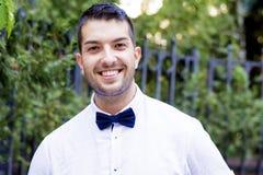 Jeune homme barbu beau avec la chemise et le noeud papillon blancs sur la rue Images stock