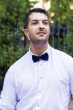 Jeune homme barbu beau avec la chemise et le noeud papillon blancs sur la rue Photo stock