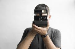 Jeune homme barbu beau dans une caméra démodée de film de chemise de cru noir de participation sur un fond et un regard blancs photo stock