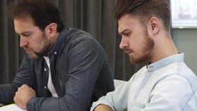 Jeune homme barbu beau parlant à son collègue mûr au bureau banque de vidéos