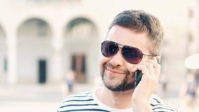 Jeune homme barbu bel parlant à son téléphone portable sur la rue Photographie stock libre de droits