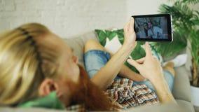 Jeune homme barbu causant avec des amis à l'aide de la tablette se trouvant dans le sofa à la maison Images stock