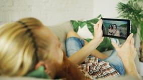 Jeune homme barbu causant avec des amis à l'aide de la tablette se trouvant dans le sofa à la maison Photos libres de droits