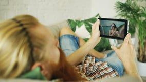 Jeune homme barbu causant avec l'amie à l'aide de la tablette se trouvant dans le sofa à la maison Images libres de droits