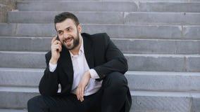 Jeune homme barbu d'affaires parlant au téléphone portable faisant des affaires se reposant sur des escaliers dans la rue image libre de droits