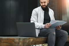 Jeune homme barbu d'affaires travaillant sur l'ordinateur portable tout en se reposant sur le banc dehors L'homme tient les docum photo stock