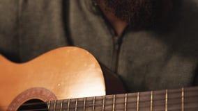 Jeune homme barbu dans le chapeau de Santa jouant la guitare se reposant devant le plan rapproché d'arbre de Noël An neuf et temp banque de vidéos