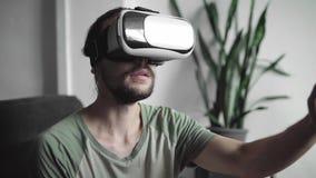 Jeune homme barbu de hippie employant son affichage de casque de VR pour le jeu de réalité virtuelle ou observant les 360 visuels