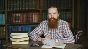 Jeune homme barbu de portrait dans la bibliothèque et regard dans l'appareil-photo photos libres de droits