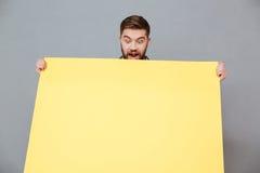Jeune homme barbu de sourire tenant le panneau de copyspace Images libres de droits