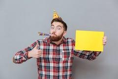 Jeune homme barbu heureux d'anniversaire tenant le panneau de copyspace Photo libre de droits