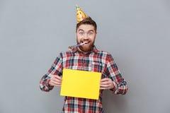 Jeune homme barbu heureux d'anniversaire tenant le panneau de copyspace Photos stock