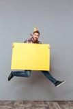 Jeune homme barbu heureux d'anniversaire tenant sauter de panneau de copyspace Images libres de droits