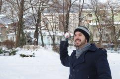 Jeune homme barbu jetant une boule de neige Photo stock