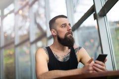 Jeune homme barbu à l'aide du téléphone portable Image stock