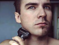 Jeune homme barbu pendant le toilettage de la barbe utilisant le trimmer Demi visage avec une moitié de barbe rasé image stock