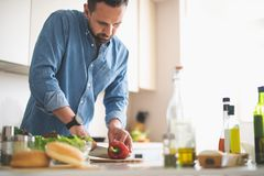 Jeune homme barbu préparant des légumes pour le dîner photographie stock