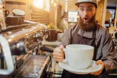 Jeune homme barbu stupéfait tenir la tasse de café blanc énorme dans des mains Il le regarde avec l'excitation Support de type au image libre de droits