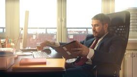 Jeune homme barbu travaillant sur son ordinateur et écrivant dans son carnet au bureau vidéo 4K clips vidéos