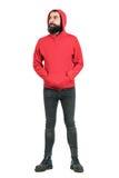 Jeune homme barbu utilisant le hoodie rouge avec des mains dans des poches regardant loin images libres de droits