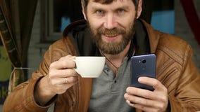 Jeune homme beau à l'aide d'un smartphone, se reposant dans un café et un café extérieurs de boissons Mouvement lent banque de vidéos
