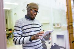 Jeune homme beau à l'aide de son comprimé numérique à la maison Photo stock