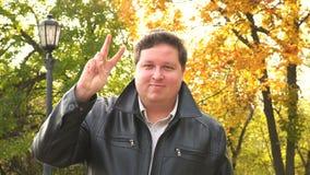 Jeune homme beau au parc de ville faisant le signe de victoire avec des doigts, sourire satisfait à l'appareil-photo banque de vidéos