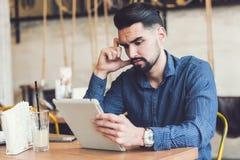 Jeune homme beau avec des écouteurs utilisant la tablette dans le café Image stock