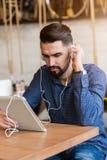 Jeune homme beau avec des écouteurs utilisant la tablette dans le café Photographie stock