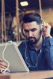 Jeune homme beau avec des écouteurs utilisant la tablette dans le café Image libre de droits