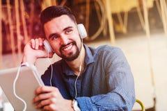 Jeune homme beau avec des écouteurs utilisant la tablette dans le café Photo stock