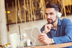 Jeune homme beau avec des écouteurs utilisant la tablette dans le café Photos stock