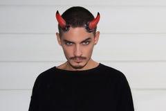 Jeune homme beau avec des klaxons de Halloween sur sa tête Photo stock