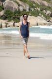 Jeune homme beau avec la barbe marchant sur la plage d'isolement Photographie stock libre de droits
