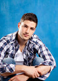 Jeune homme beau avec la chemise de plaid sur le bleu Photos libres de droits