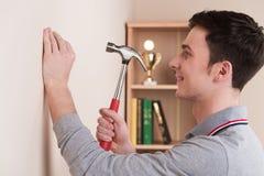 Jeune homme beau avec le marteau à la maison Photo libre de droits