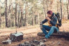 jeune homme beau avec le sac à dos buvant du thé chaud du thermos tout en se reposant sur le rondin photographie stock libre de droits