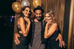 Jeune homme beau avec les amis féminins à la boîte de nuit Photographie stock libre de droits