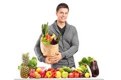 Jeune homme beau avec un sac des épiceries se tenant derrière un pil Images stock