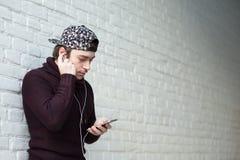 Jeune homme beau avec un smartphone et des écouteurs Image libre de droits