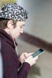 Jeune homme beau avec un smartphone et des écouteurs dans la causerie en ligne photo libre de droits