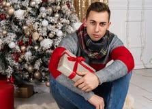 Jeune homme beau avec une écharpe se reposant avec des cadeaux sur le plaid près de l'arbre de Noël images stock