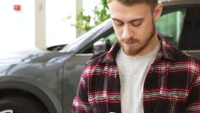 Jeune homme beau barbu à l'aide du téléphone intelligent tout en achetant la nouvelle voiture au concessionnaire banque de vidéos