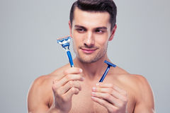 Jeune homme beau choisissant le rasoir Photos stock