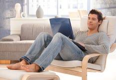 Jeune homme beau détendant à la maison avec l'ordinateur portatif Photo libre de droits